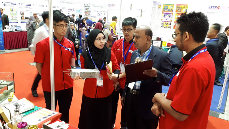 Ms. Dayang explaining her team's innovation product to the judge at the ITEX'17