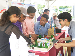 Md. Pilus (second left) talking to IUKL architecture students at the building model exhibition booth at the Student Village.