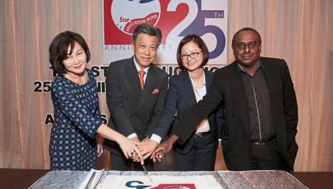 (From left) June, Wong, Wang and Terence cutting the 25th anniversary cake.